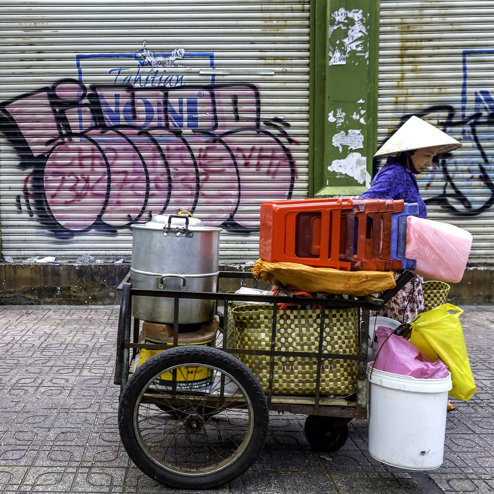 Le Thi Lang transports food to her streetside spot for lunch service which is around the corner from the apartment.
